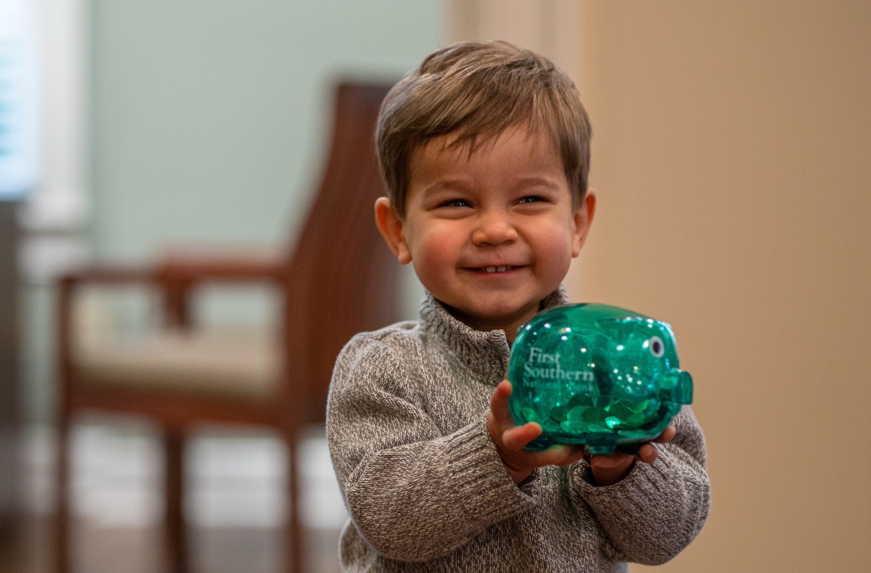 little boy holds a piggy bank with First Southern on it